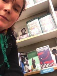 En leende kvinna framför en bokhylla