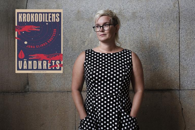 Författaren i svartvit prickig klänning framför betongvägg. Bokens omslag på väggen.