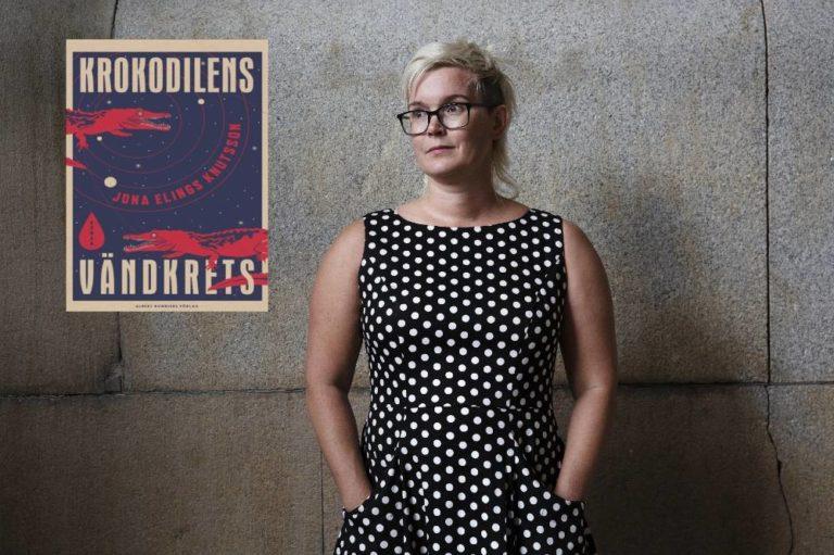 Kvinna i prickig klänning framför betongvägg med bild på bokomslag